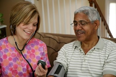 A young nurse checks blood pressure on senior man